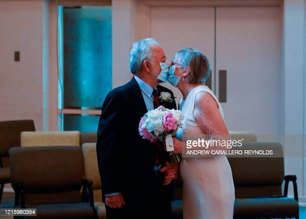 Linda Delk and Ardell Hoveskeland kiss through their masks before their socially distanced wedding, with family and friends joining over ZOOM, at the...