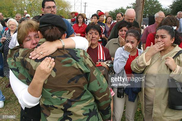 Linda Gomez hugs her daughter, Spc. Rebecca Vasquez, as the soldier's Aunt Lupe Bledsoe, sister Regina Gomez and cousin Lisa Garcia look on during an...
