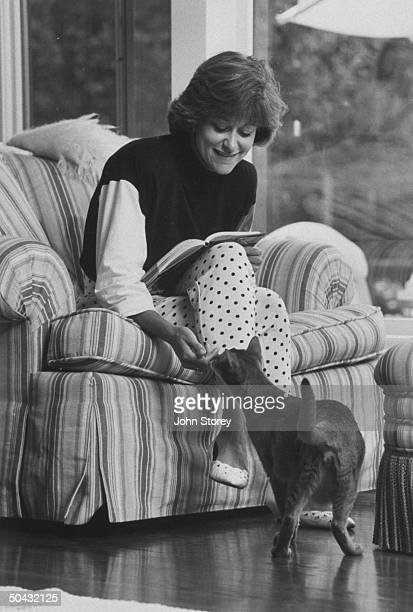 Linda Gray Sexton novelist biographer of her poet mother Anne Sexton holding book on her lap as she reaches down to pet her cat while sitting in an...
