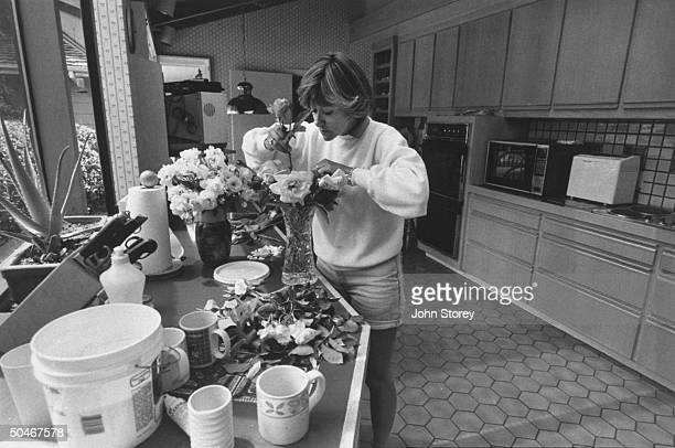 Linda Gray Sexton novelist biographer of her poet mother Anne Sexton arranging roses from her garden in vases on counter of her kitchen at home