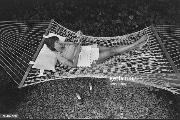 Linda Gray Sexton novelist biographer of her poet mother Anne Sexton reading as she lies in hammock in yard at home