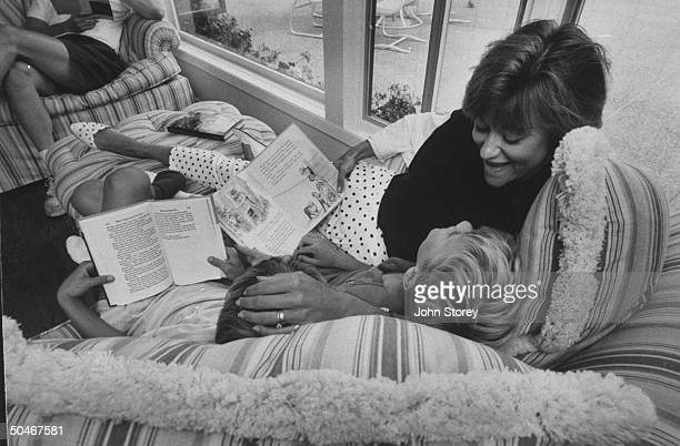 Linda Gray Sexton novelist biographer of her poet mother Anne Sexton snuggling on couch w young sons Alexander Nicholas as they read books together...