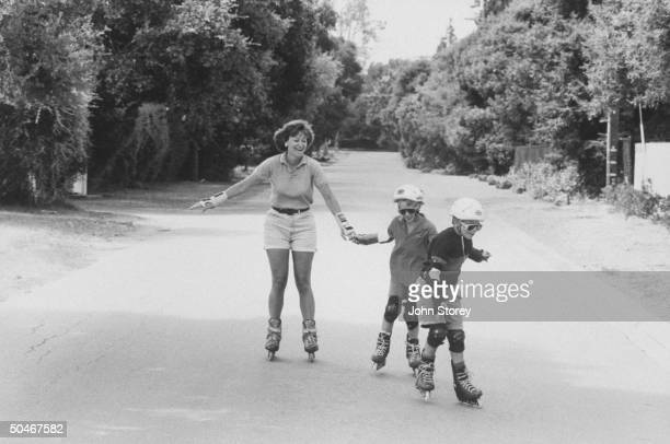 Linda Gray Sexton novelist biographer of her poet mother Anne Sexton rollerblading w her young sons Nicholas Alexander in street at home
