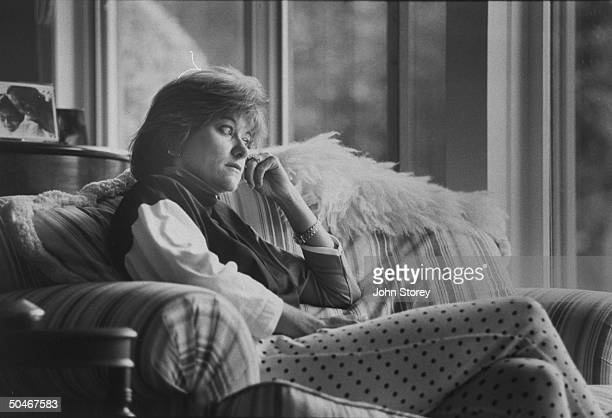 Linda Gray Sexton novelist biographer of her poet mother Anne Sexton posing pensively on couch in living room at home