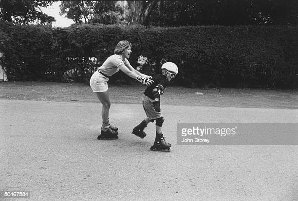 Linda Gray Sexton novelist biographer of her poet mother Anne Sexton rollerblading w her young son Alexander in street at home