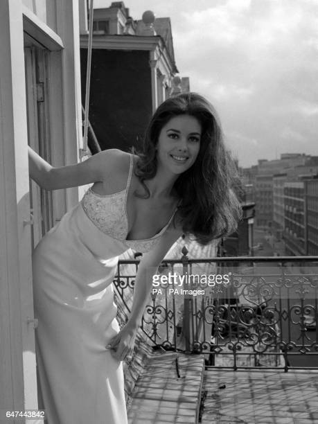 Linda Harrison looking out over the London scene in a pure white silk dress with embroidered bodice. Linda is starring in the Hollywood film 'Planet...