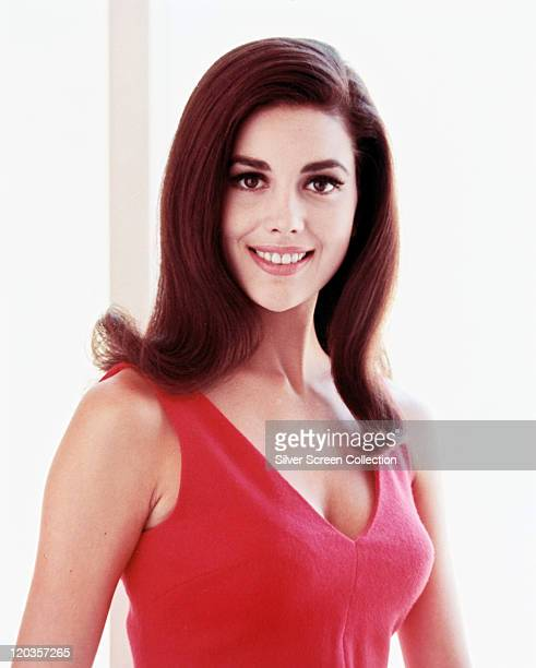Linda Harrison, US actress and model, smiling, wearing a pink vest top, in a studio portrait, against a white background, circa 1965.