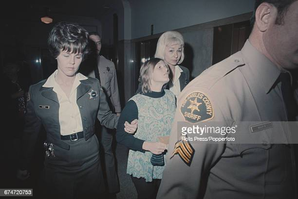 Linda Kasabianone of the accused in the Sharon Tate and LaBianca murder cases is escorted by police officers and court officials through the Hall of...