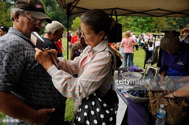 Linda Kelly uses her husband Bobby's chest as support to write a check to the Pancreatic Action Network prior to a memorial service for Patrick...