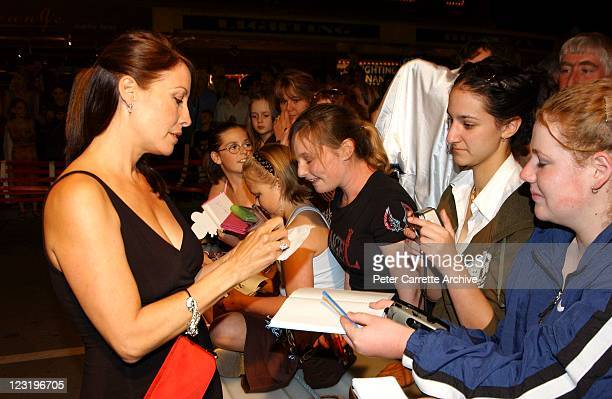 Linda Kozlowski signs autographs for fans as she arrives for the world premiere of the film 'Strange Bedfellows' featuring her husband Paul Hogan at...