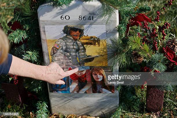Linda Lamie of Georgia points to the grave of her son Sgt Gene L Lamie on Veteran's Day at Arlington National Cemetery on November 11 2012 in...
