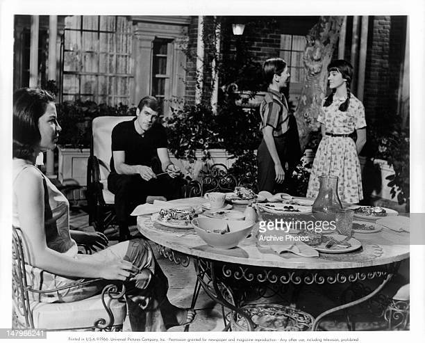 Linda Lawson and Robert Pickering sitting near outdoor table as Pat Cardi clowns with Mary Badham in a scene from the film 'Let's Kill Uncle Before...