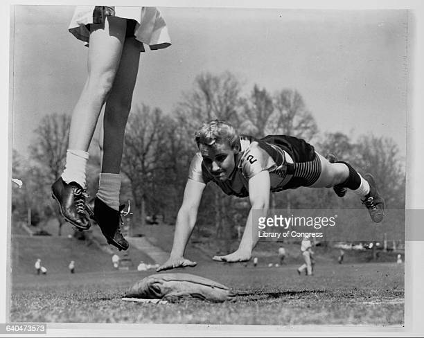 Linda McConkey of the Lorelei Ladies dives headfirst for third base during an exhibition game The legs of Jerrie Rainey are visible as she leaps for...