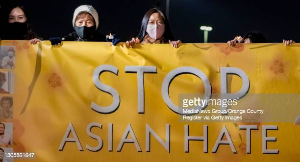 Linda Nguyen, right, a victim of Asian hate, joins members of the Vietnamese community and others hold up a banner against Asian hate during a...