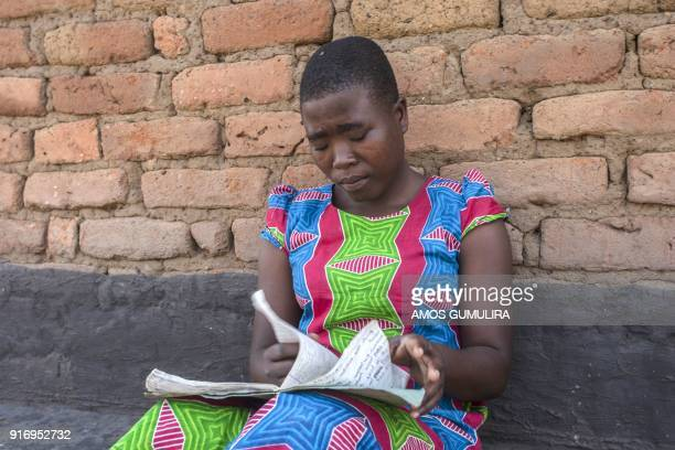 Linda Nowa a Form Four student reads her books during a visit to her home village of Chadza in the area of Chief Kabudula in Lilongwe Malawi on...