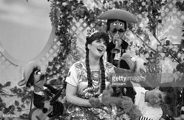 Linda Ronstadt and popular muppet Elmo sing with mariachi style muppets on Sesame Street A puppeteer moves Elmo from just out of camera range