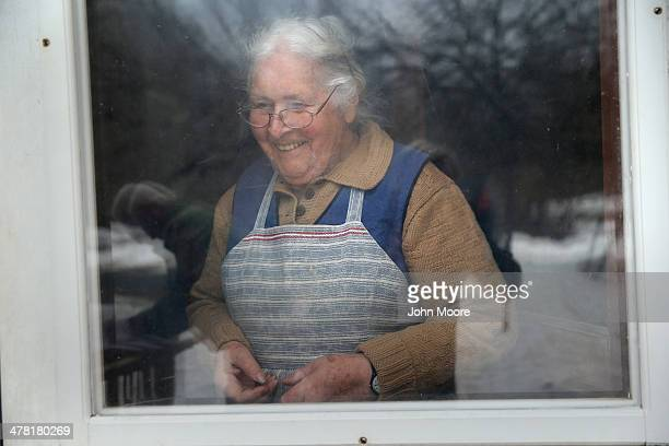 Linda Scheidegger happily receives a 'meals on wheels' food delivery from Catholic Charities staffer Tom Neville on March 12 2014 in Montague New...
