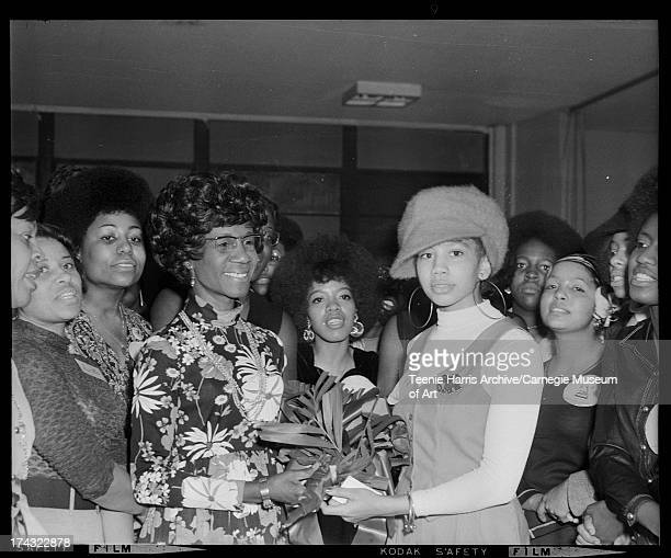 Linda Starkey handing bouquet to Shirley Chisholm surrounded by Delta Sigma Theta sorority members including Christine Jones Fulwiley on left Vivian...