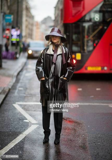 Linda Tol is seen wearing Ganni bucket hat black vinyl coat outside Christopher Kane during London Fashion Week February 2019 on February 18 2019 in...
