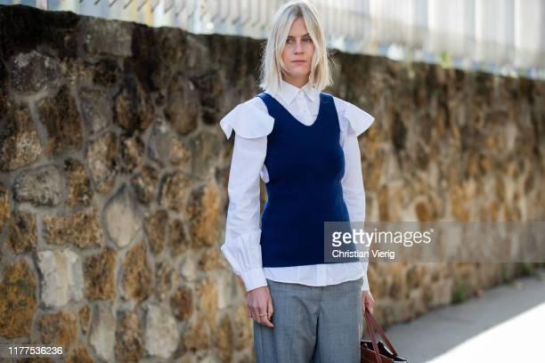 Linda Tol seen wearing white button shirt, blue slip over, grey pants, Loewe bag outside Loewe during Paris Fashion Week Womenswear Spring Summer...