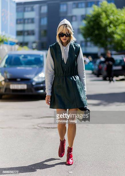 Linda Tol wearing a grey hoody and sleeveless vneck leather dress outside Ganni during the second day of the Copenhagen Fashion Week Spring/Summer...
