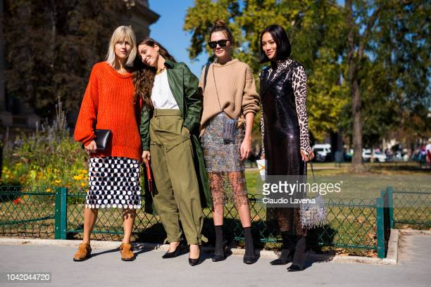 Linda Tol wearing a red sweater sequin midi skirt brown shoes and black bag Erika Boldrin wearing a white tshirt army green pants green coat black...