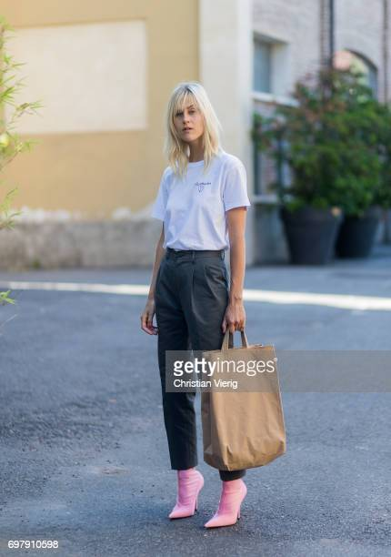 Linda Tol wearing a white tshirt denim jeans pink boots brown bag is seen outside Malibu 1992 during Milan Men's Fashion Week Spring/Summer 2018 on...