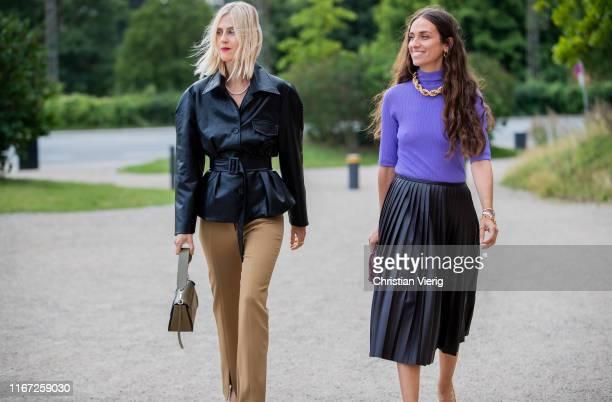 Linda Tol wearing black belted leather jacket brown pants and Erika Boldrin wearing purple turtleneck black pleated skirt is seen outside Samsøe...