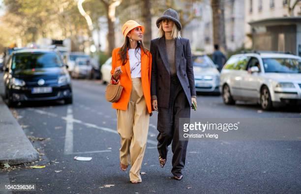 Linda Tol wearing grey hat and Chloe Harrouche wearing Prada bucket hat and orange blazer is seen outside Koche during Paris Fashion Week Womenswear...