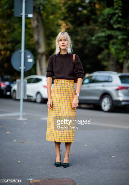 Linda Tol wearing knit checked yellow midi skirt is seen outside Tods during Milan Fashion Week Spring/Summer 2019 on September 21 2018 in Milan Italy