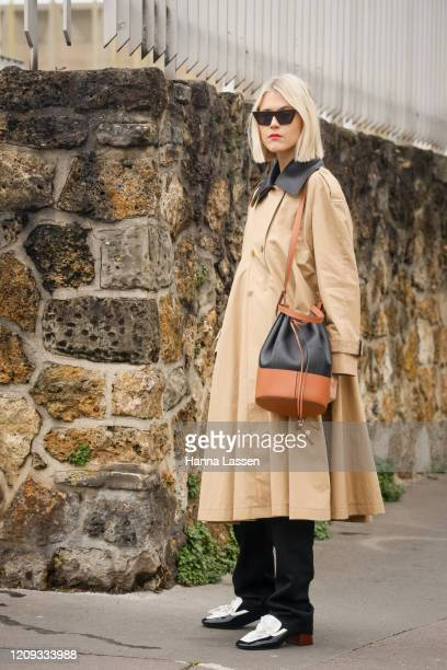 Linda Tol wearing sunglasses, beige coat, black pants and Loewe shoes outside the Loewe show during the Paris Fashion Week Womenswear Fall/Winter on...