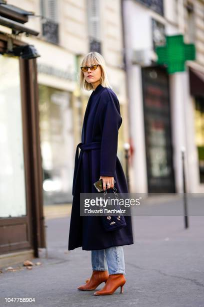 Linda Tol wears a blue coat, a bag, brown shoes, blue jeans, outside Altuzarra, during Paris Fashion Week Womenswear Spring/Summer 2019, on September...