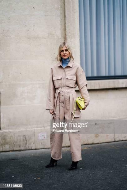 Linda Tol wears a blue Loewe turtleneck, a powder pink jumpsuit, a lemon-yellow wristlet bag, black high heeled boots, outside Nina Ricci, during...