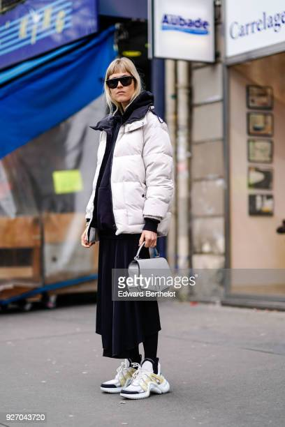 Linda Tol wears a white puffer coat a black dress sunglasses a gray bag sneakers during Paris Fashion Week Womenswear Fall/Winter 2018/2019 on March...