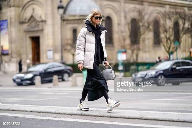 Linda Tol wears a white puffer coat a black dress sunglasses a gray bag sneakers during Paris Fashion Week Womenswear Fall/Winter 2018/2019 on March...