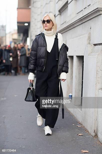 Linda Tol wears a white turtleneck black jumpsuit and black puffer jacket off one sleeve uring Milan Men's Fashion Week Fall/Winter 2017/18 on...