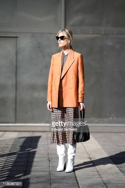 Linda Tol wears an orange blazer jacket, a checked dress, white boots, a black bag, sunglasses, during London Fashion Week February 2019 on February...