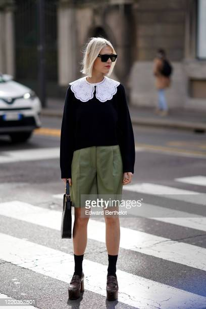 Linda Tol wears sunglasses, a bag, white large collar with embroidery, a black top, green shorts, socks, brown leather shoes, outside Sportmax,...