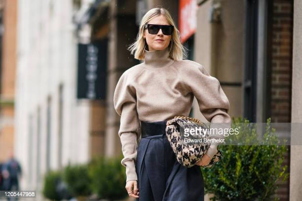 Linda Tol wears sunglasses a gray turtleneck pullover with puff sleeves a black and white houndstooth pattern tweed bag dark pants during New York...