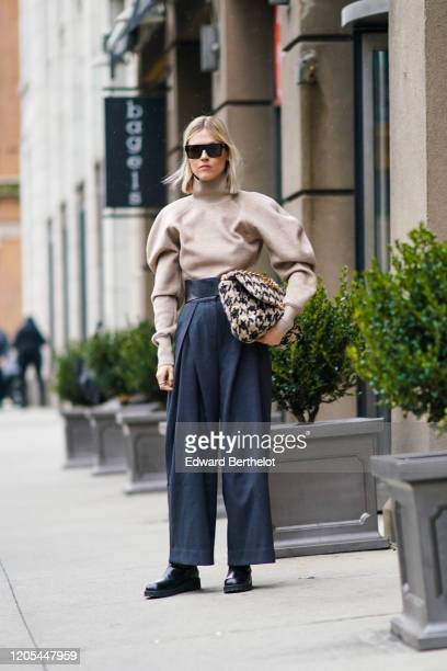 Linda Tol wears sunglasses a gray turtleneck pullover with puff sleeves a black and white houndstooth pattern tweed bag dark pants black leather...