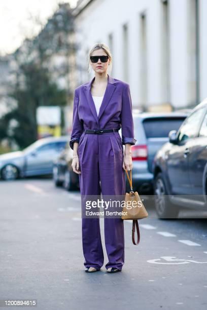 Linda Tol wears sunglasses, a purple jumpsuit, a white t-shirt, a brown leather bag, shoes, outside Schiaparelli, during Paris Fashion Week - Haute...