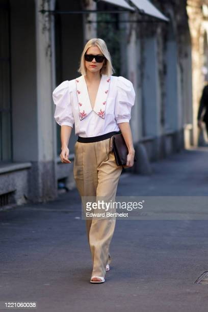 Linda Tol wears sunglasses a white shirt with ruffled puff shoulders and red floral print beige flare pants a brown leather clutch white shoes...