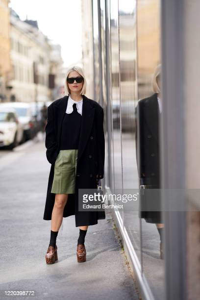 Linda Tol wears sunglasses, an oversized black long jacket, a bag, white large collar, a black top, green shorts, socks, brown leather shoes, outside...