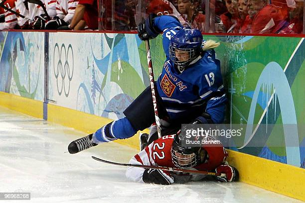 Linda Valimaki of Finland gets a hooking penalty against Hayley Wickenheiser of Canada during the ice hockey women's semifinal game on day 11 of the...