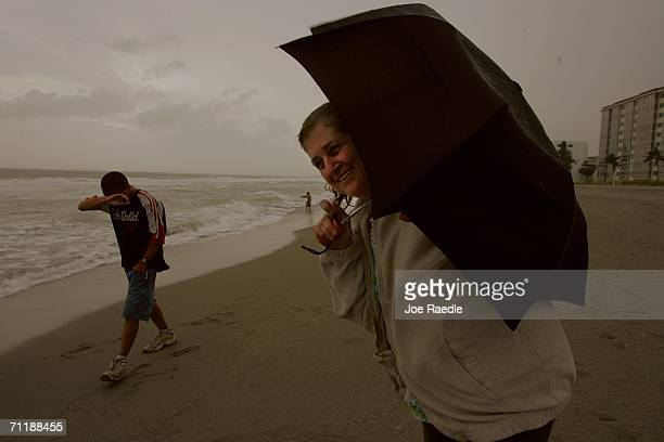 Linda Wheeler uses her umbrella to shield herself from blowing sand kicked up by the winds from Tropical Storm Alberto in the Gulf of Mexico June 12...