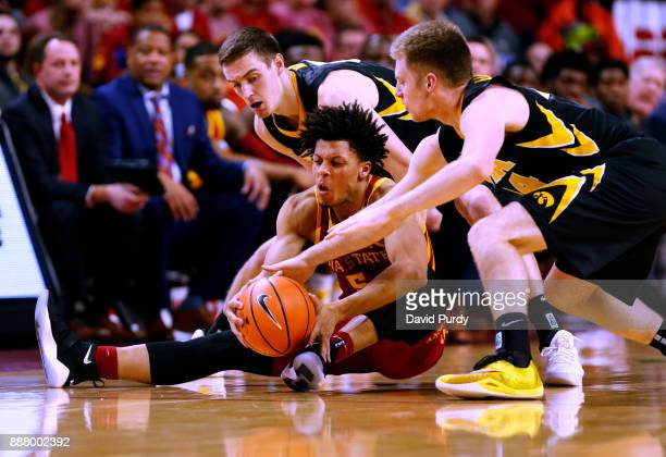 Lindell Wigginton of the Iowa State Cyclones battle for the ball with Nicholas Baer of the Iowa Hawkeyes left and Brady Ellingson of the Iowa...