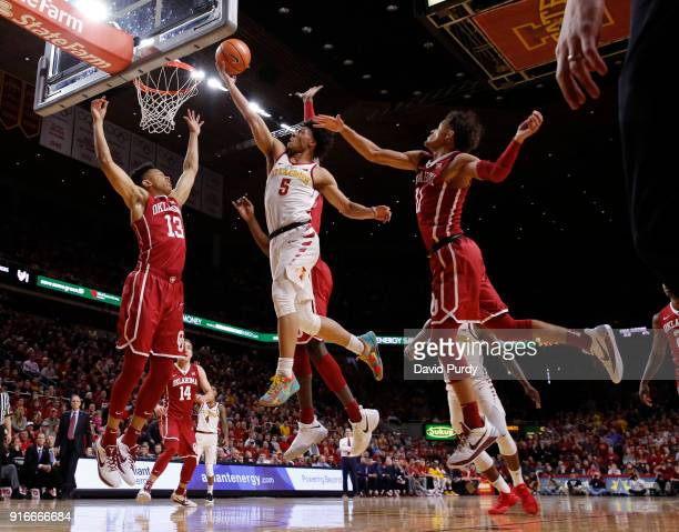 Lindell Wigginton of the Iowa State Cyclones lays up a shot as Jordan Shepherd and Trae Young of the Oklahoma Sooners block in the first half of play...