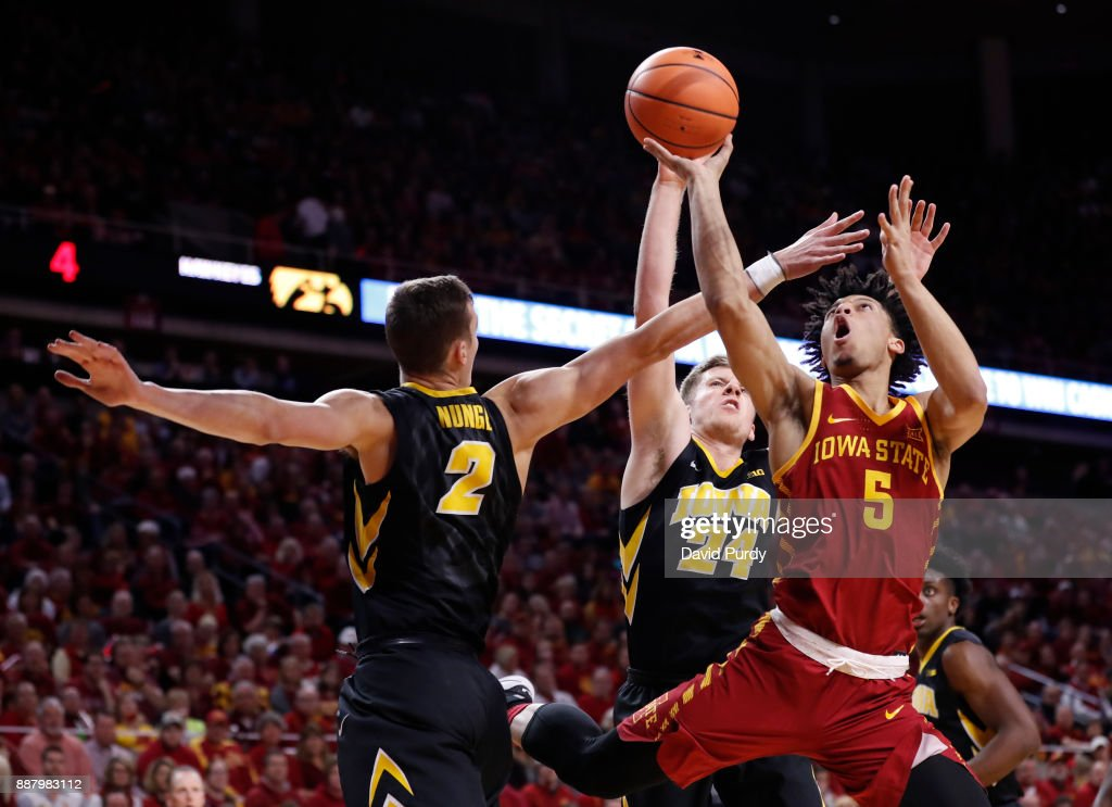 Lindell Wigginton #5 of the Iowa State Cyclones takes a shot as Jack Nunge #2 of the Iowa Hawkeyes, and Brady Ellingson #24 of the Iowa Hawkeyes block in the first half of play at Hilton Coliseum on December 7, 2017 in Ames, Iowa.