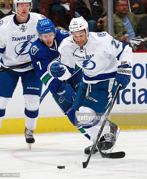 Linden Vey of the Vancouver Canucks checks JT Brown of the Tampa Bay Lightning during their NHL game at Rogers Arena October 18 2014 in Vancouver...