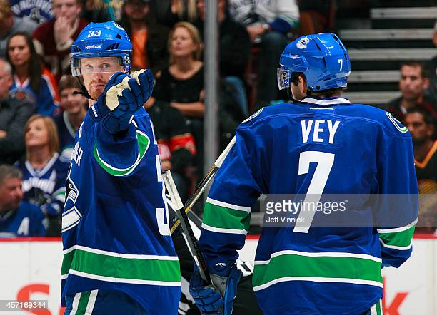 Linden Vey of the Vancouver Canucks listens to teammate Henrik Sedin during their NHL game against the Edmonton Oilers at Rogers Arena October 11...